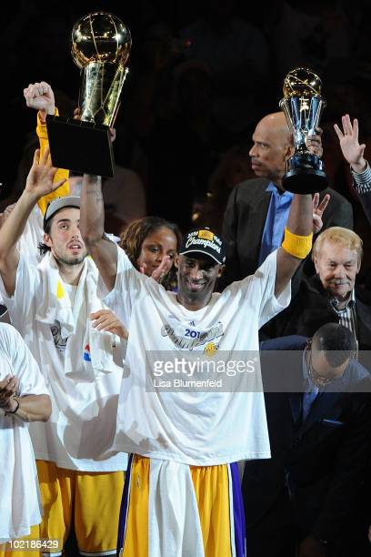 Kobe Bryant of the Los Angeles Lakers holds both the Larry O'Brien trophy and the Bill Russell Finals MVP trophy after the Lakers defeated the Boston...