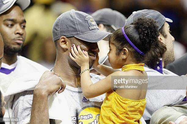 Kobe Bryant of the Los Angeles Lakers holds his daughter Gianna after the Lakers defeated the Orlando Magic in Game Five of the 2009 NBA Finals on...
