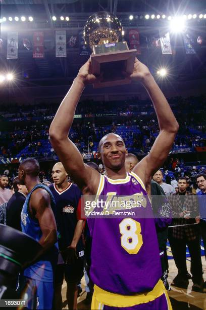 Kobe Bryant of the Los Angeles Lakers holds his trophy overhead after winning first place in the NBA All-Star Slam Dunk Contest at Gund Arena on...