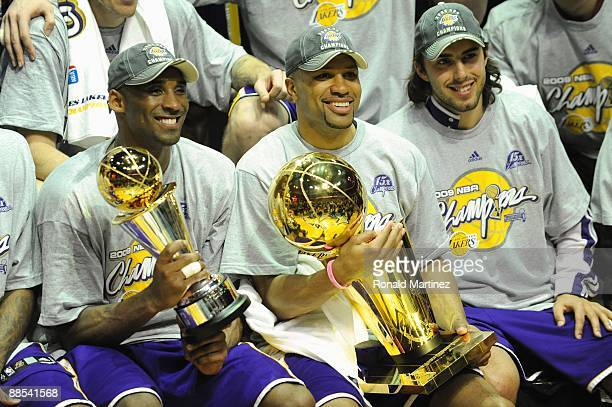 Kobe Bryant of the Los Angeles Lakers holds the Bill Russell MVP trophy and Derek Fisher of the Lakers holds the Larry O'Brien trophy after defeating...
