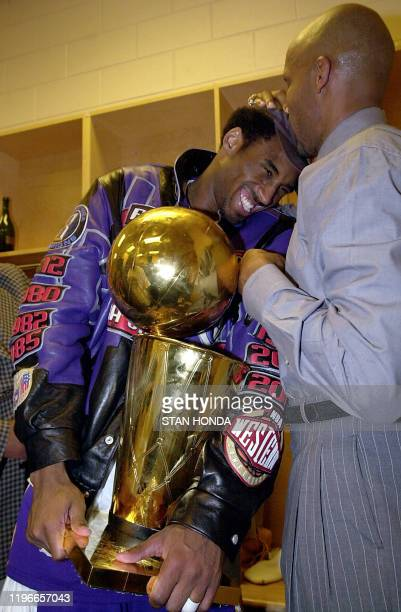 Kobe Bryant of the Los Angeles Lakers holds the championship trophy as teammate Ron Harper kisses his head after winning game five of the NBA Finals...