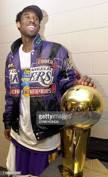 Kobe Bryant of the Los Angeles Lakers holds the championship trophy after winning game five of the NBA Finals against the Philadelphia 76ers 15 June...