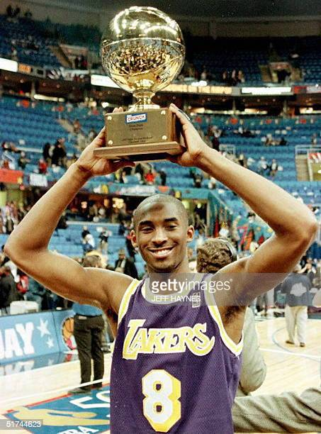 Kobe Bryant, of the Los Angeles Lakers, holds the trophy for winning the NBA Slam Dunk contest 08 February at Gund Arena in Cleveland, Ohio. Bryant...