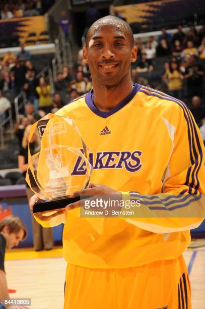 Kobe Bryant of the Los Angeles Lakers holds up a performance award presented by Kia Motors recognizing him as the Western Conference player of the...