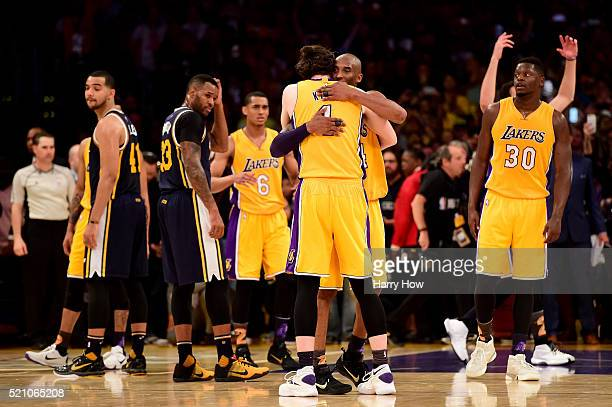 Kobe Bryant of the Los Angeles Lakers hugs teammate Ryan Kelly as Bryant is taken out of the game after scoring 60 points against the Utah Jazz at...