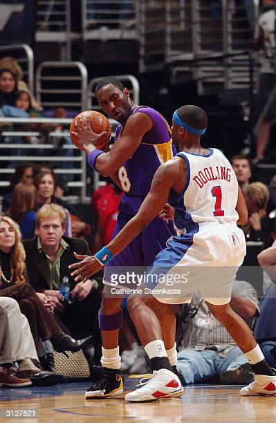 Kobe Bryant of the Los Angeles Lakers is defended by Keyon Dooling of the Los Angeles Clippers during the game at Staples Center on March 17 2004 in...
