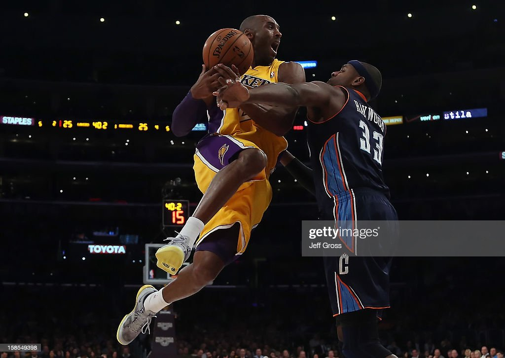 Kobe Bryant #24 of the Los Angeles Lakers is fouled by Brendan Haywood #33 of the Charlotte Bobcats while driving to the basket in the first half at Staples Center on December 18, 2012 in Los Angeles, California. The Lakers defeated the Bobcats 101-100.