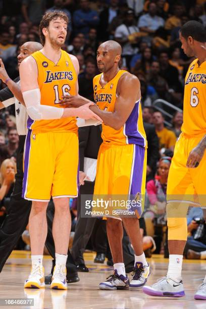 Kobe Bryant of the Los Angeles Lakers is helped up by teammate Pau Gasol after getting injured during their game against the Golden State Warriors at...