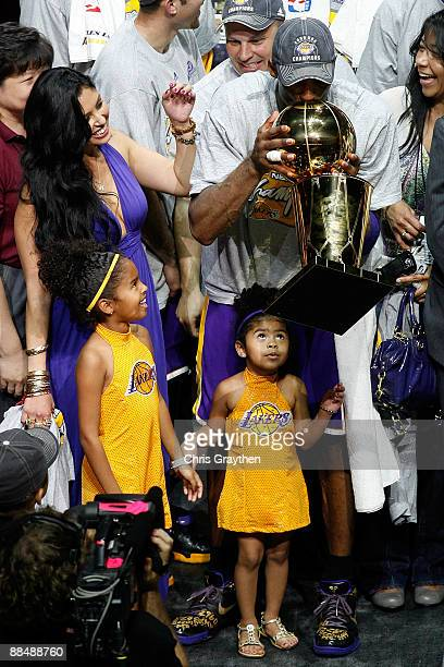 Kobe Bryant of the Los Angeles Lakers kisses the Larry O' Brien Trophy with his wife Vanessa and his daughters Natalia and Gianna after the Lakers...
