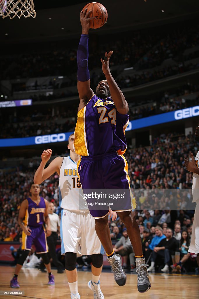Kobe Bryant #24 of the Los Angeles Lakers lays up a shot against Nikola Jokic #15 of the Denver Nuggets at Pepsi Center on December 22, 2015 in Denver, Colorado.