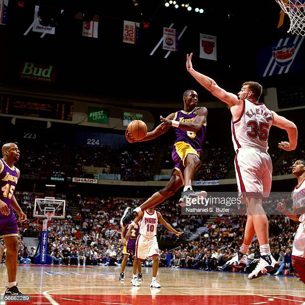 Kobe Bryant of the Los Angeles Lakers leaps to the basket against Joe Kleine of the New Jersey Nets March 24 1997 at the Continental Airliines Arena...