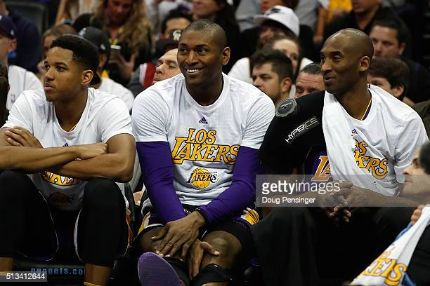 Kobe Bryant of the Los Angeles Lakers looks on from the bench with teammates Metta World Peace and Anthony Brown of the Los Angeles Lakers as he sat...