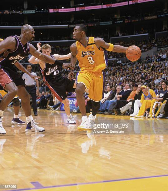 Kobe Bryant of the Los Angeles Lakers looks to drive around Karl Malone of the Utah Jazz during the game at Staples Center on December 8, 2002 in Los...