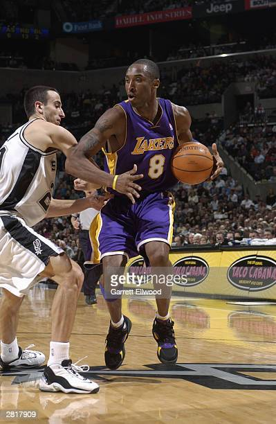 Kobe Bryant of the Los Angeles Lakers looks to make a move on Emanuel Ginobili of the San Antonio Spurs at SBC Center on December 3 2003 in San...
