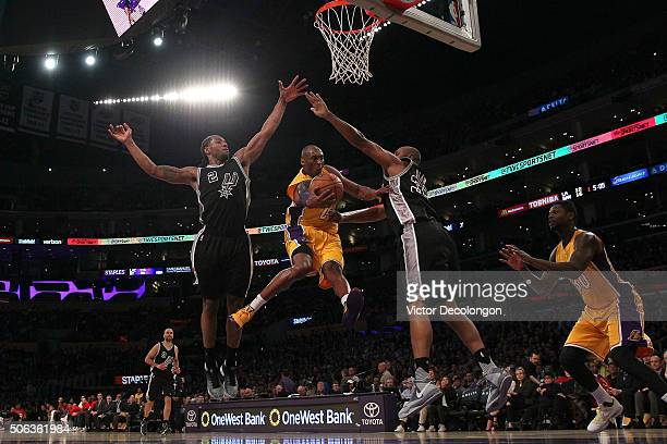 Kobe Bryant of the Los Angeles Lakers looks to make a pass between Kawhi Leonard and Boris Diaw of the San Antonio Spurs during the NBA game at...