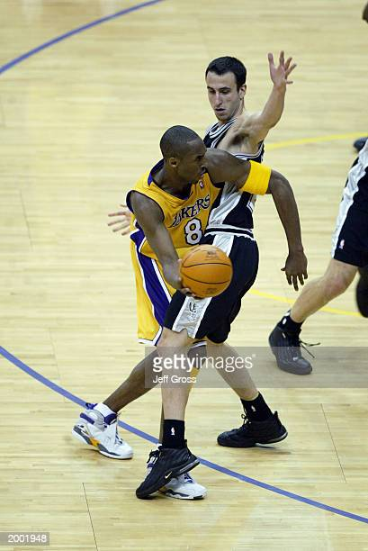 Kobe Bryant of the Los Angeles Lakers looks to pass around Emanuel Ginobili of the San Antonio Spurs in Game three of the Western Conference...