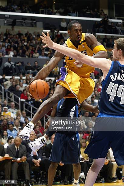 Kobe Bryant of the Los Angeles Lakers looks to pass around Sean Bradley of the Dallas Mavericks during the NBA game at the Staples Center on December...