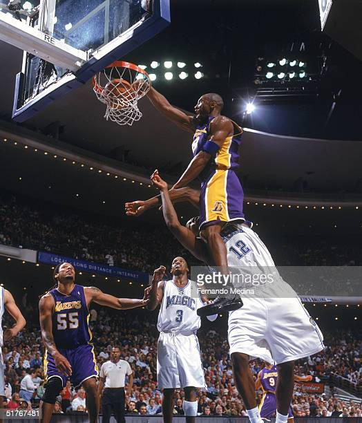 Kobe Bryant of the Los Angeles Lakers makes a dunk against Dwight Howard of the Orlando Magic at TD Waterhouse Centre on November 12 2004 in Orlando...