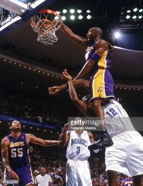 Kobe Bryant of the Los Angeles Lakers makes a dunk against Dwight Howard of the Orlando Magic at TD Waterhouse Centre on November 12, 2004 in...