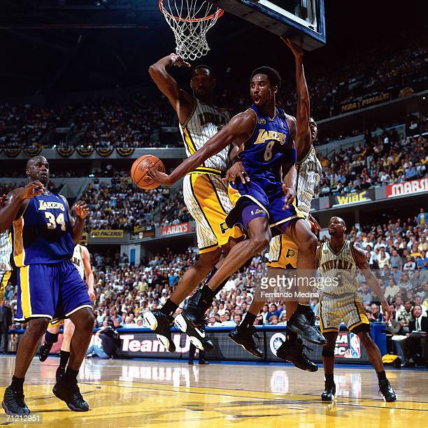 Kobe Bryant of the Los Angeles Lakers makes a pass to teammate Shaquille O'Neal of the Los Angeles Lakers while being defended by Travis Best of the...