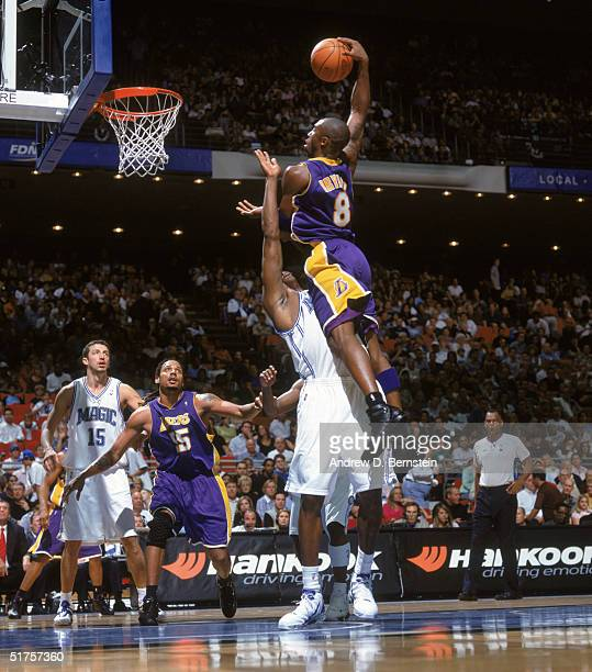 Kobe Bryant of the Los Angeles Lakers moves for a dunk over Dwight Howard of the Orlando Magic at the TD Waterhouse Centre on November 12 2004 in...