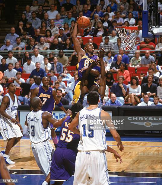 Kobe Bryant of the Los Angeles Lakers moves for a dunk over Dwight Howard of the Orlando Magic at the TD Waterhouse Centre on November 12, 2004 in...