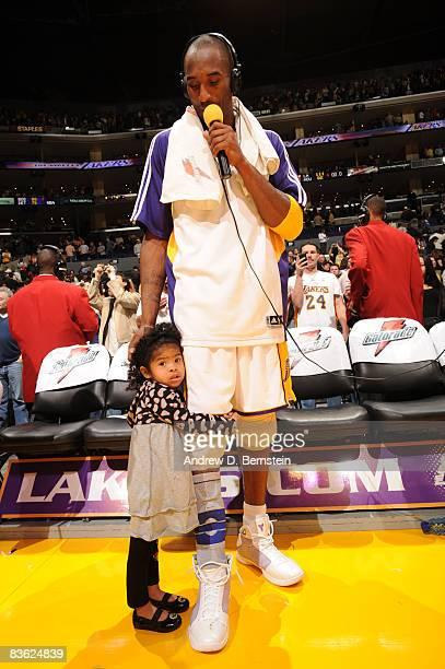 Kobe Bryant of the Los Angeles Lakers participates in a postgame interview while his daughter Gianna stands with him following the Lakers' victory...