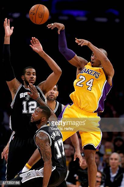 Kobe Bryant of the Los Angeles Lakers passes the ball past Jonathon Simmons and LaMarcus Aldridge of the San Antonio Spurs during the first half of a...