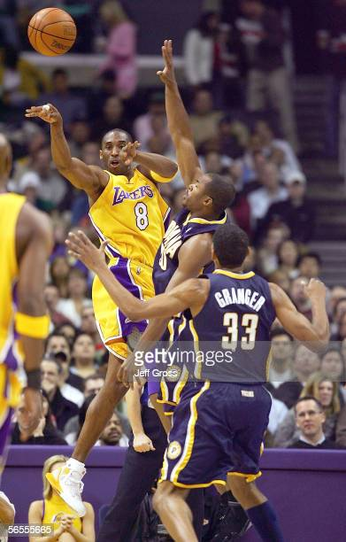 Kobe Bryant of the Los Angeles Lakers passes the ball while being guarded by Fred Jones of the Indiana Pacers during the first half of the game at...