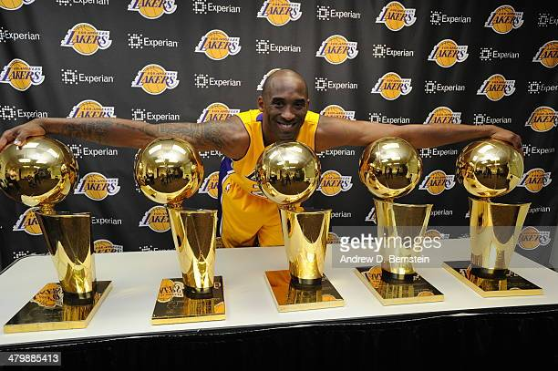 Kobe Bryant of the Los Angeles Lakers poses for a picture with his 5 NBA Championship trophies at STAPLES Center on March 20 2014 in Los Angeles...
