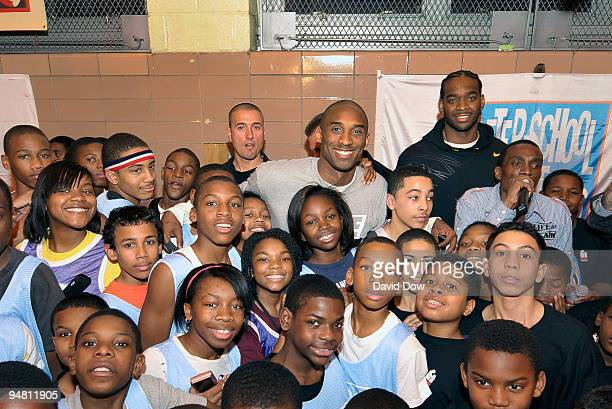 Kobe Bryant of the Los Angeles Lakers poses for photographs with fans during a community relations event at the Junior High School 45 East Harlem on...