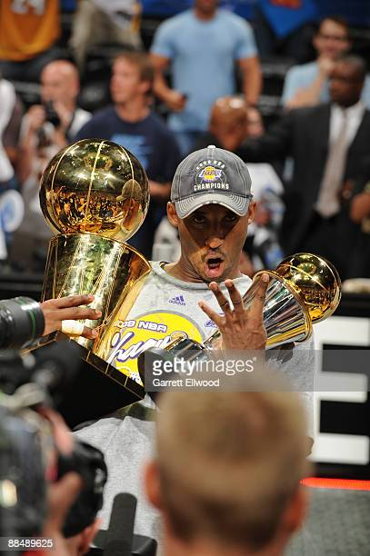 Kobe Bryant of the Los Angeles Lakers poses with the Larry O' Brien and Bill Russell MVP trophy after defeating the Orlando Magic in Game Five of the...