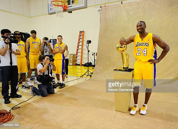 Kobe Bryant of the Los Angeles Lakers poses with the NBA Finals Larry O'Brien Championship Trophy during Media Day at the Toyota Center on September...
