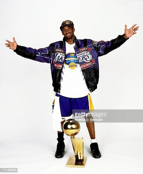 Kobe Bryant of the Los Angeles Lakers proudly stands over the NBA championship trophy and celebrates a day after the Lakers defeated the Philadelphia...