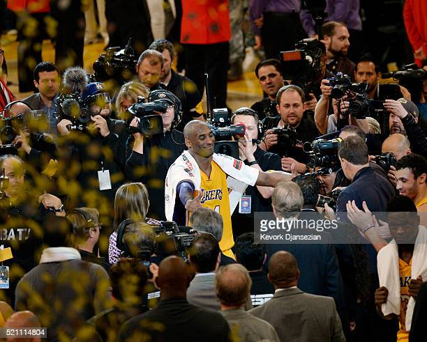 Kobe Bryant of the Los Angeles Lakers reaches out to hugs his children after retiring from basketball and scoring 60 points against the Utah Jazz at...