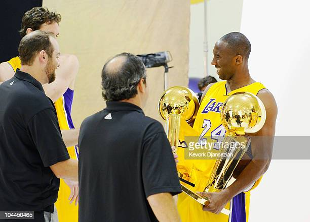 Kobe Bryant of the Los Angeles Lakers reacts after receiving two NBA Finals Larry O'Brien Championship Trophy's from Lakers photographers Noah Graham...