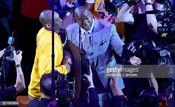 Kobe Bryant of the Los Angeles Lakers reacts meets with Magic Johnson who spoke to the crowd ahead of Kobe's last game for the Lakers against the...