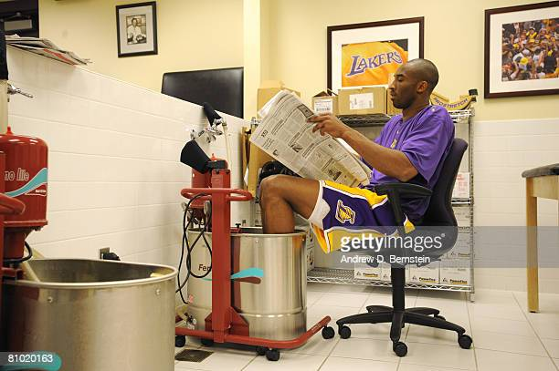 Kobe Bryant of the Los Angeles Lakers reads the newspaper while soaking his feet in the whirlpool before taking on the Utah Jazz in Game Two of the...