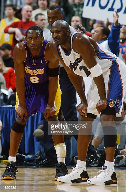 Kobe Bryant of the Los Angeles Lakers rests next to Michael Jordan of the Washington Wizards during the NBA game at the MCI Center on November 8 2002...