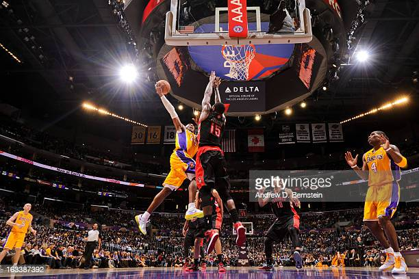 Kobe Bryant of the Los Angeles Lakers rises for a dunk against Amir Johnson of the Toronto Raptors at Staples Center on March 8 2013 in Los Angeles...