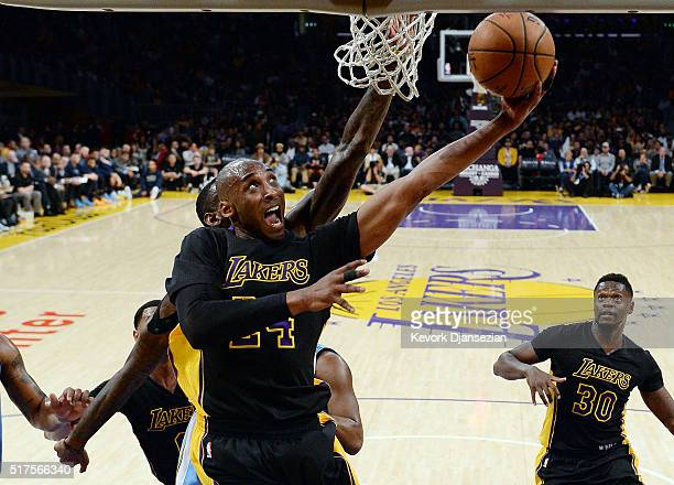 Kobe Bryant of the Los Angeles Lakers scores a basket against JaKarr Sampson of the Denver Nuggets during the first half of the basketball game at...