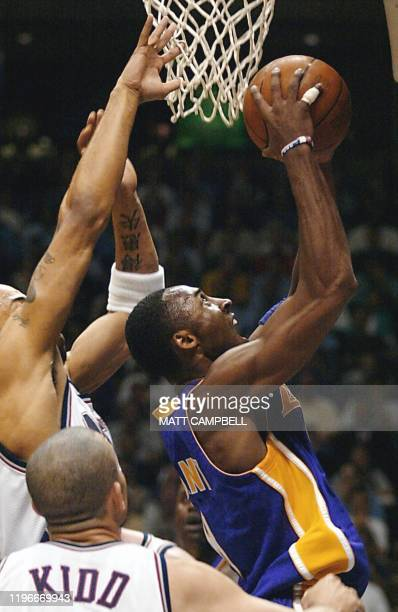 Kobe Bryant of the Los Angeles Lakers scores in front of Jason Kidd of the New Jersey Nets during the first quarter in game four of the NBA Finals at...