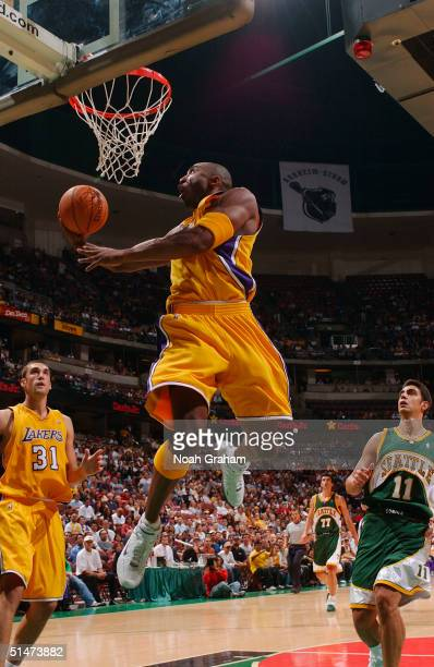 Kobe Bryant of the Los Angeles Lakers scores the basket on a reverse layup past Ibrahim Kutluay of the Seattle Supersonics on October 12, 2004 in...