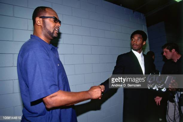Kobe Bryant of the Los Angeles Lakers shakes hands with his dad Joe Bryant during Game Four of the First Round of the 1998 NBA Playoffs on April...