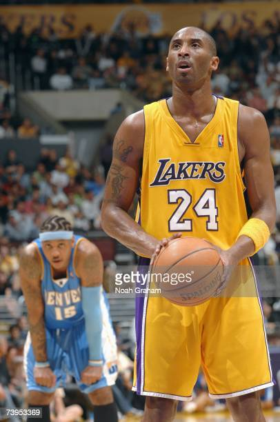 Kobe Bryant of the Los Angeles Lakers shoots a free throw while Carmelo Anthony of the Denver Nuggets stands in the background at Staples Center on...