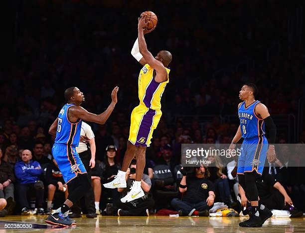 Kobe Bryant of the Los Angeles Lakers shoots a jumper between Kevin Durant and Russell Westbrook of the Oklahoma City Thunder during the first half...