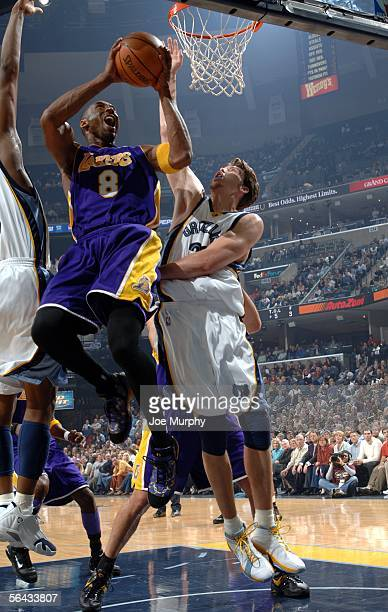 Kobe Bryant of the Los Angeles Lakers shoots a layup over Mike Miller of the Memphis Grizzlies on December 14 2005 at FedExForum in Memphis Tennessee...