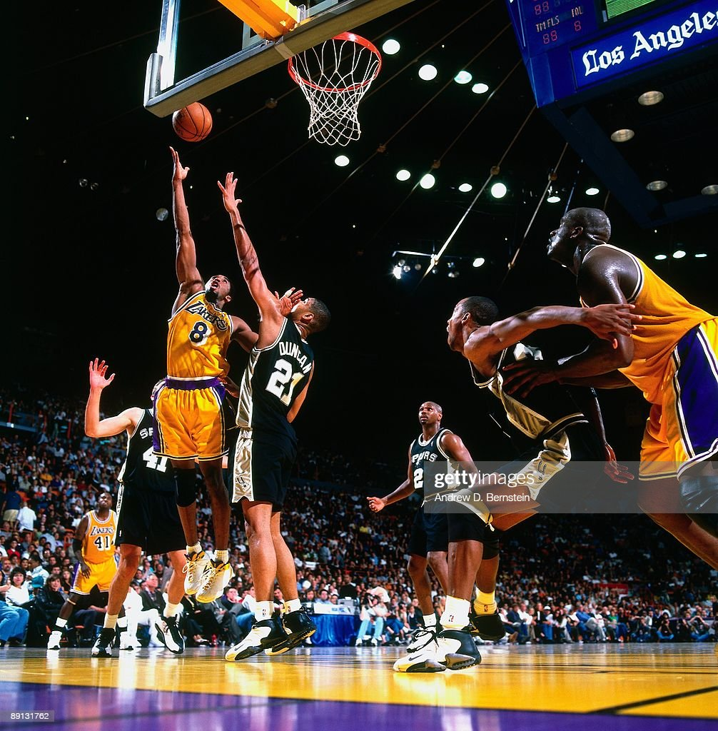 4f3ab399c Kobe Bryant of the Los Angeles Lakers shoots a layup over Tim Duncan ...