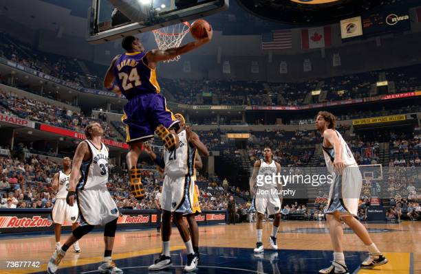 Kobe Bryant of the Los Angeles Lakers shoots a layup past Mike Miller and Hakim Warrick of the Memphis Grizzlies on March 22 2007 at FedExForum in...