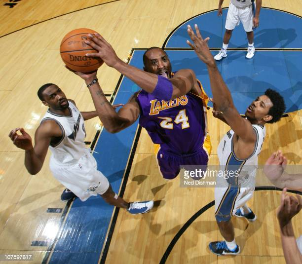 Kobe Bryant of the Los Angeles Lakers shoots against Gilbert Arenas and Nick Young of the Washington Wizards at the Verizon Center on December 14...